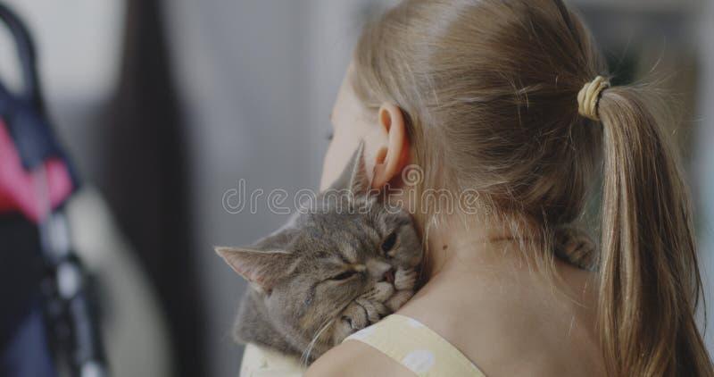 Katten som ligger på flickor, knuffar arkivfoto