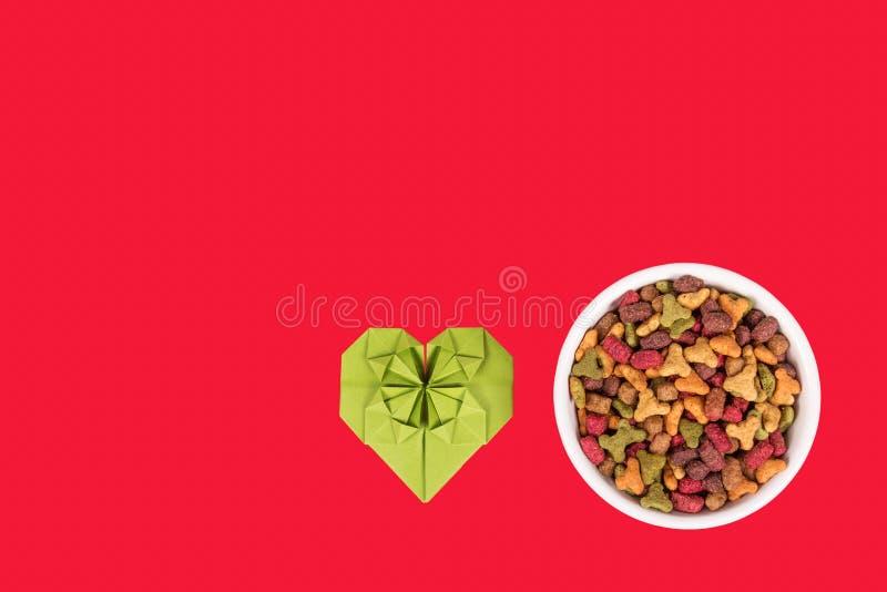 Kattenvoedsel en hart Kom droog kattenvoedsel Liefdekat Rode achtergrond stock foto's