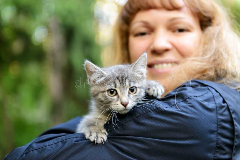 Kattunge på flickans skuldra royaltyfri foto