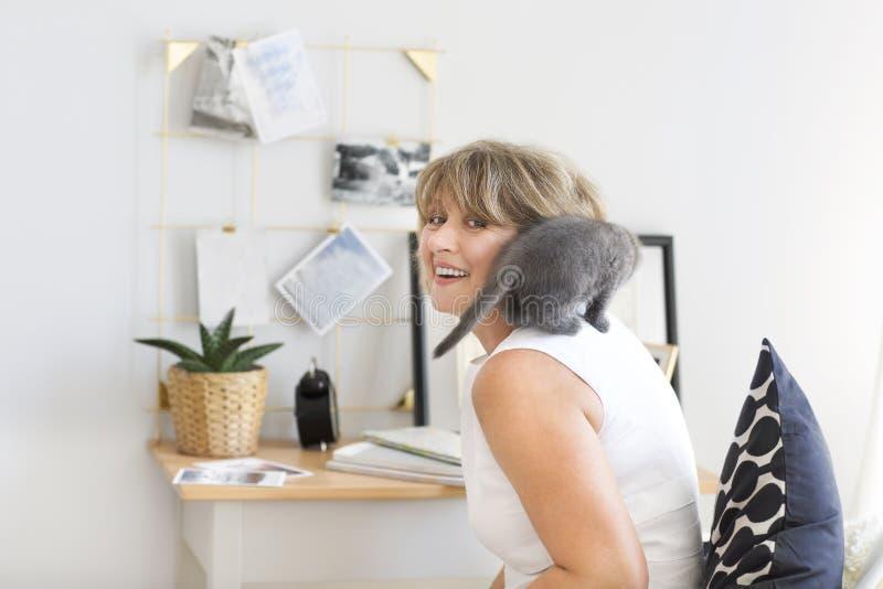 Kattungesammanträde på skuldran av en mogen kvinna arkivfoto