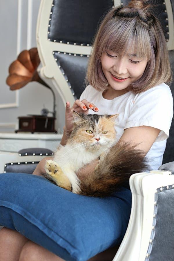 Kattvänbegrepp Härlig asiatisk kvinna som sitter på soffan och bär en katt på hans hand med förälskelse gullig flicka för katt arkivfoton