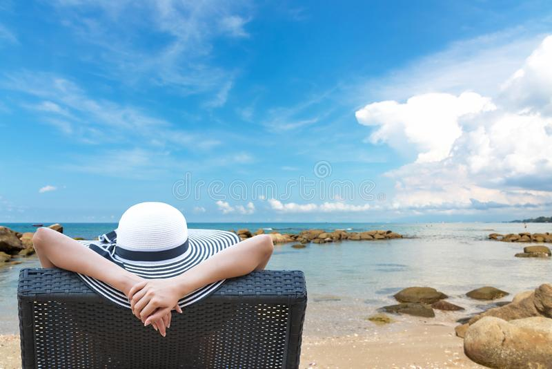 katya krasnodar夏天领土假期 美丽的年轻亚裔妇女松弛和愉快在海滩睡椅假日夏令时,天空蔚蓝背景 免版税库存照片