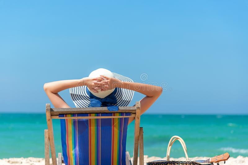 katya krasnodar夏天领土假期 美丽的年轻亚裔妇女松弛和愉快在海滩睡椅用鸡尾酒椰子汁在假日夏天,蓝色 库存图片