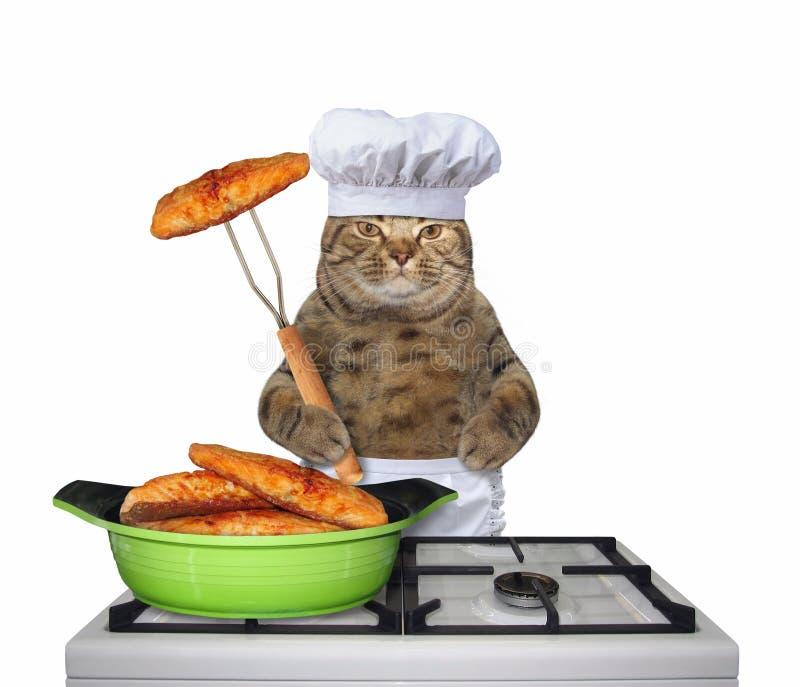 Katze kocht gebratene Fische auf einem Ofen lizenzfreie stockfotos