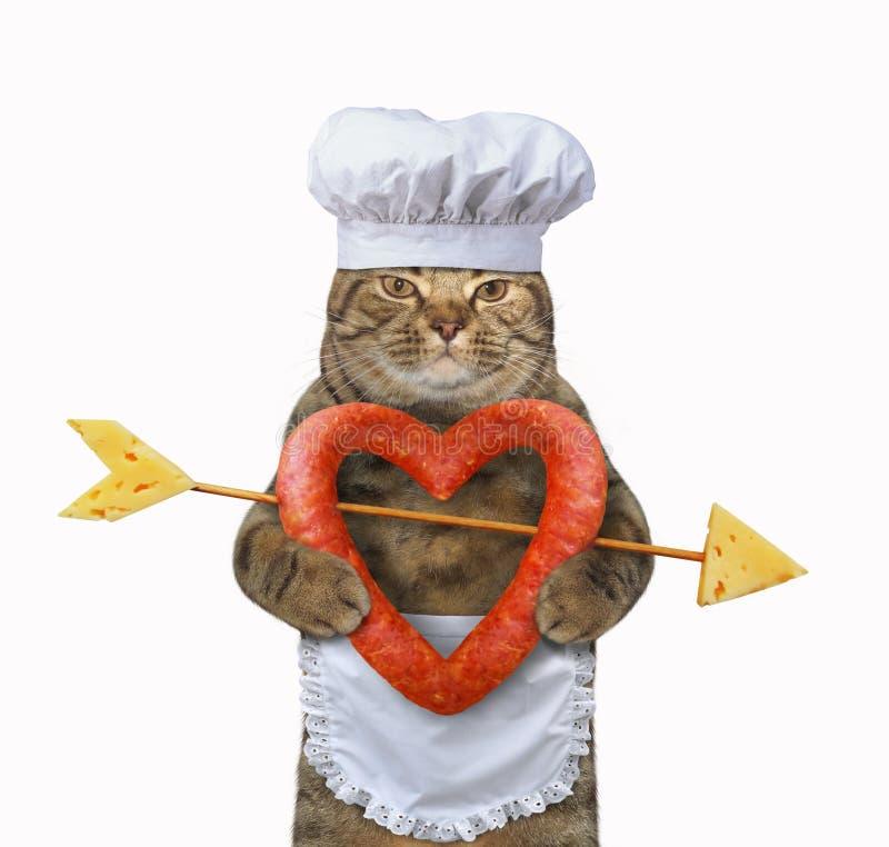Katzenkoch hält eine geformte Wurst des Herzens lizenzfreie stockfotografie