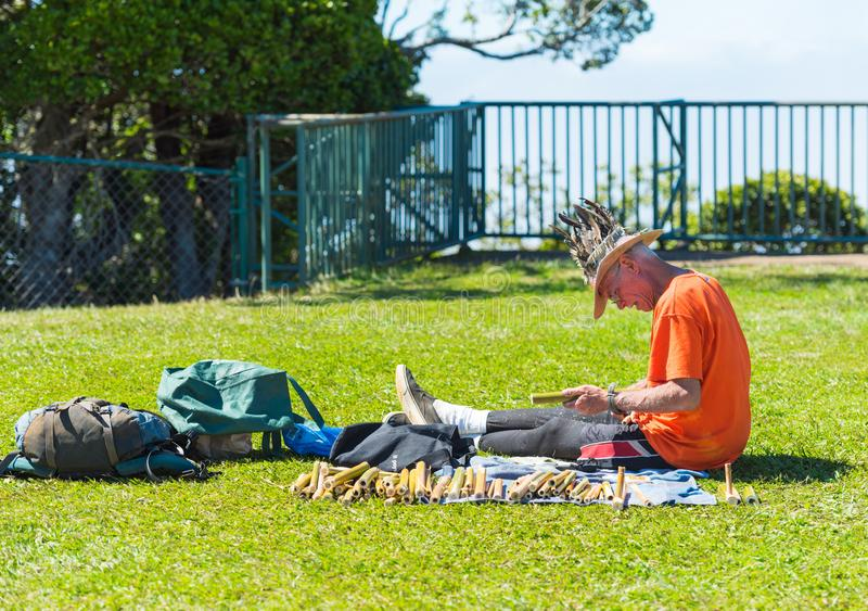 KAUAI, HAWAII - FEBRUARY 9, 2018: A man with bamboo tubes sits on the lawn. With selective focus royalty free stock images