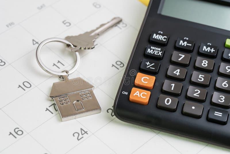 Kauf des neuen Hauses, Hypothekenzeitplananzeige oder Immobilienzahlungstag, silberner Hausschlüsselring mit Taschenrechner auf w lizenzfreie stockfotos