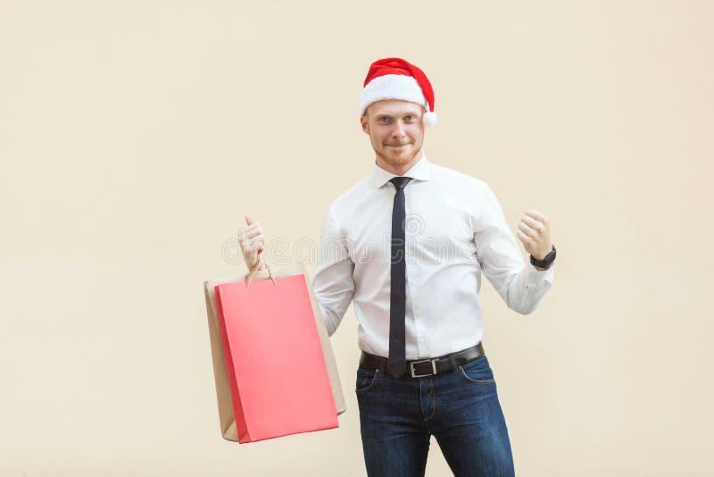 Kauf für besten Preis im Winter Junger Erwachsener und Bartmann in rotem Sankt-Hut, Glück, das Kamera betrachtet lizenzfreies stockfoto