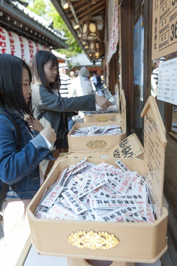 Kaufen Sie innerhalb des shintoistischen Schreins und des buddhistischen Tempels in Japan, das Omikuji oder Falze mit Vermögenn f lizenzfreie stockfotos