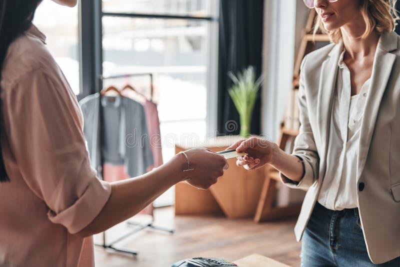 Kaufen und Verkauf Schließen Sie oben von der jungen Frau, die eine Kreditkarte gibt stockfotografie