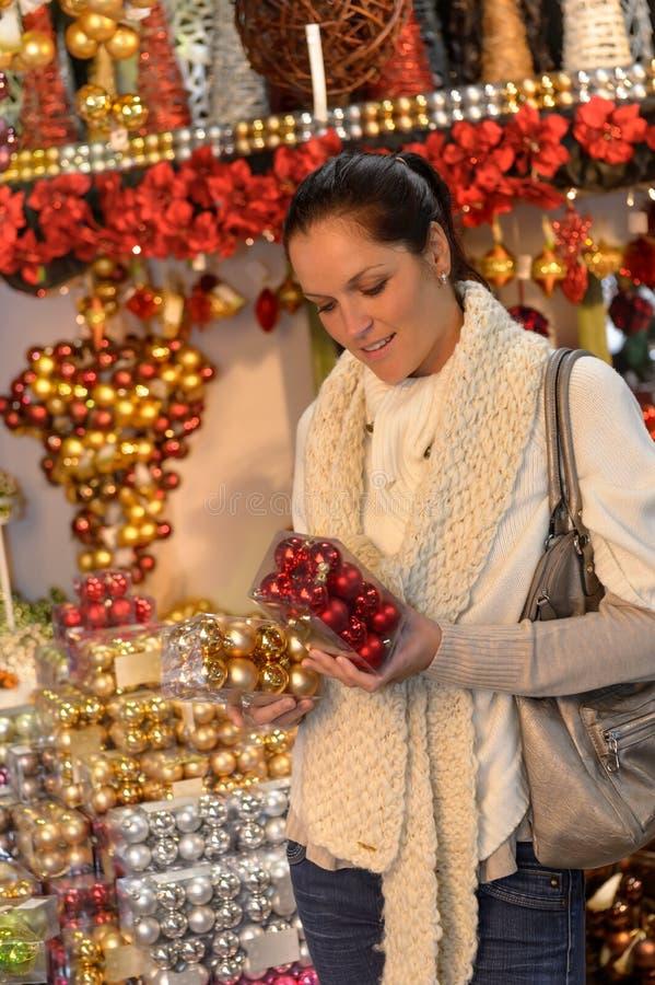Kaufende Bälle der jungen Frau Weihnachtsim Geschäft lizenzfreies stockfoto