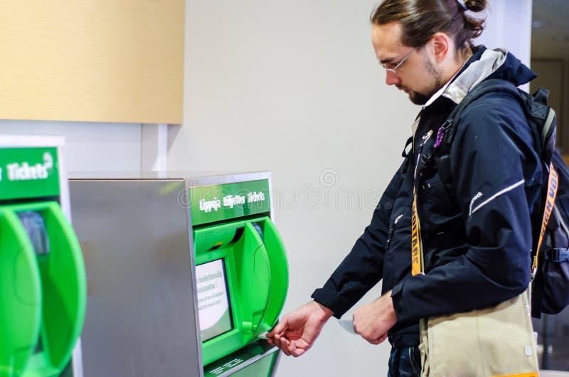 Kaufende Bahnfahrkarte des jungen Mannes stockbild