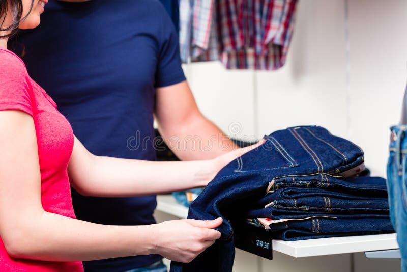 Kaufende Blue Jeans der Paare im Shop lizenzfreie stockbilder