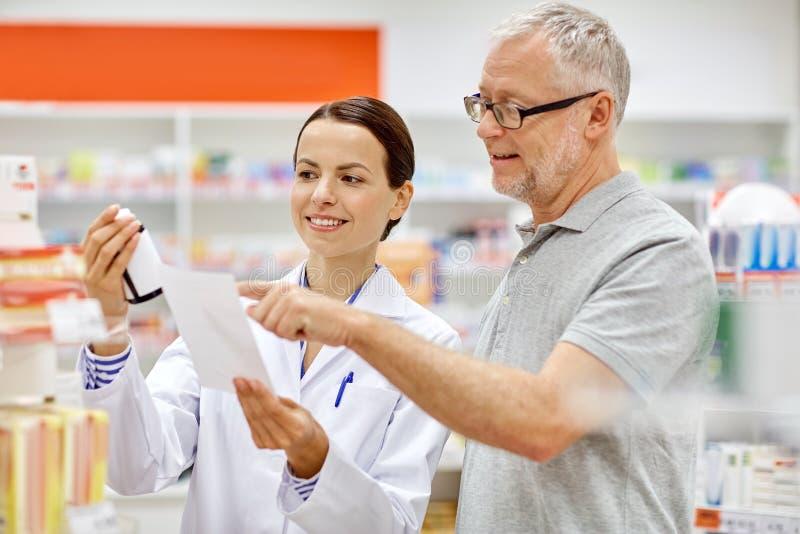 Kaufende Droge des Apothekers und des älteren Mannes an der Apotheke lizenzfreie stockfotos