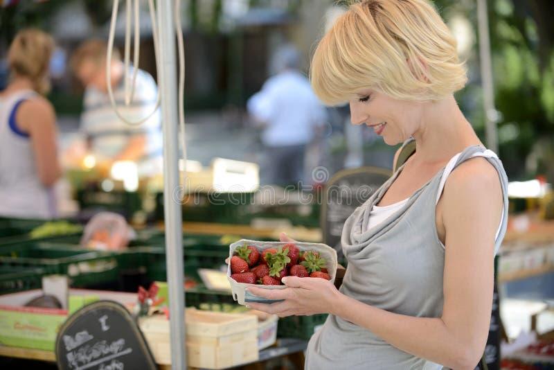 Kaufende Erdbeeren der Frau am Markt des Landwirts stockfotografie