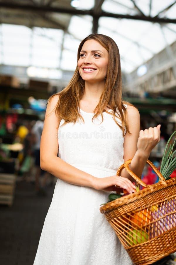 Kaufende gesunde Nahrung der jungen Frau auf dem Markt lizenzfreie stockbilder
