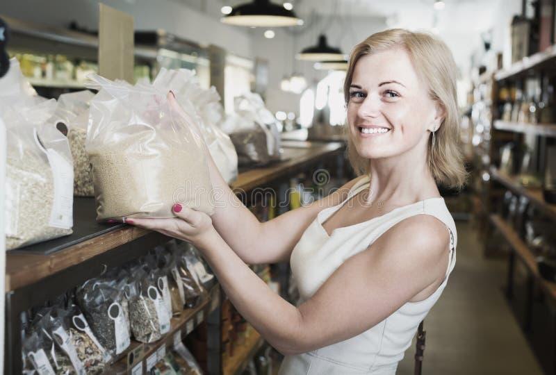 Kaufende Getreide der Frau im Gemischtwarenladen lizenzfreie stockbilder