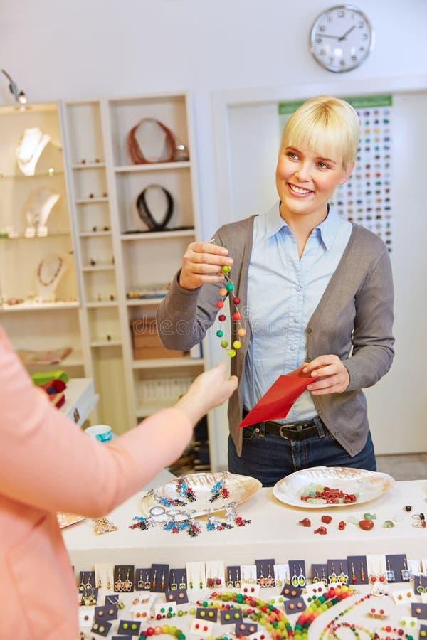 Kaufende Halskette der Frau in einem Schmuck lizenzfreie stockfotos