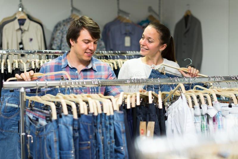 Kaufende Jeans der Paare im Einkaufszentrum stockbilder