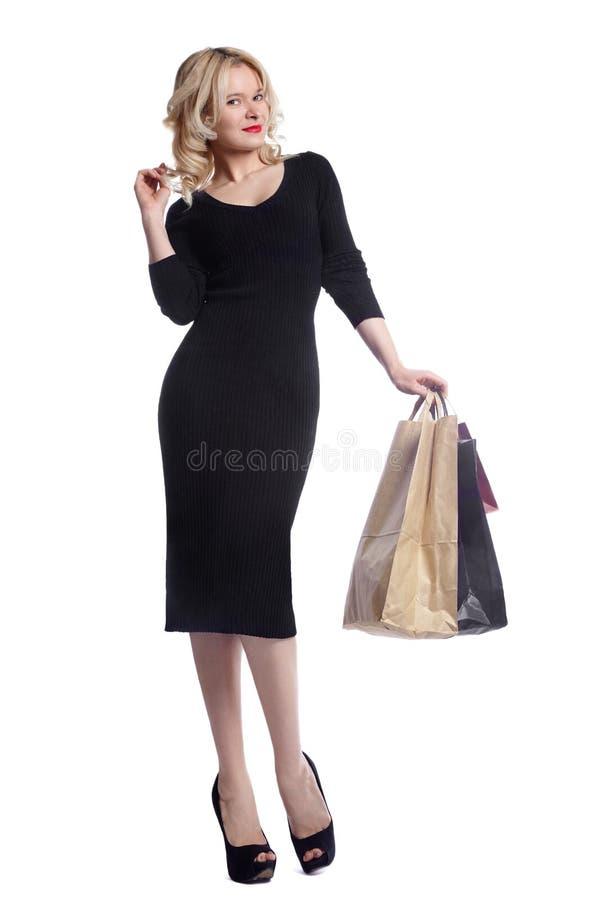 Kaufende junge Frau, die Taschen lokalisiert auf weißem Studiohintergrund hält Liebesmode und -verkäufe Glückliches blondes Mädch lizenzfreie stockfotos