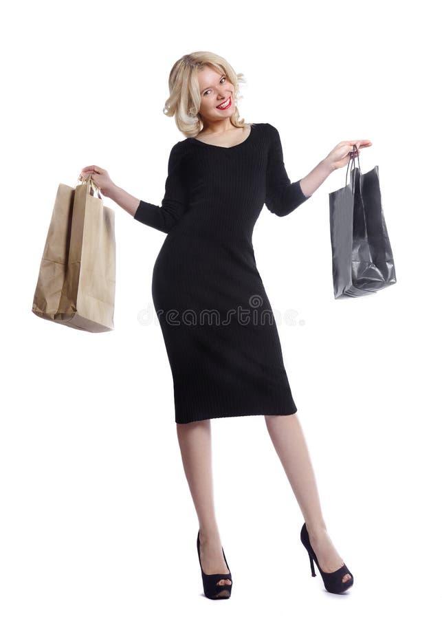 Kaufende junge Frau, die Taschen lokalisiert auf weißem Studiohintergrund hält Liebesmode und -verkäufe Glückliches blondes Mädch lizenzfreie stockfotografie