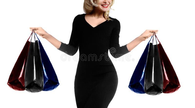 Kaufende junge Frau, die Taschen lokalisiert auf weißem Studiohintergrund hält Verkaufstapete shopaholic stockfoto