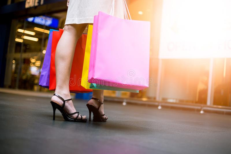 Kaufende junge schöne glückliche Frau der Asiatin mit farbigen Taschen im Mall stockfotos