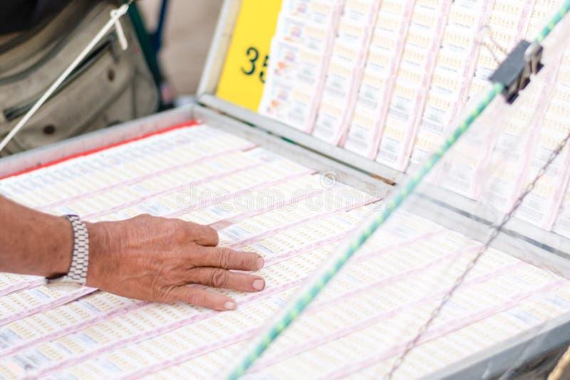 Kaufende Lotterie des Mannes am Zähler Thailändische Lotterie bietet eine Form von an stockbild