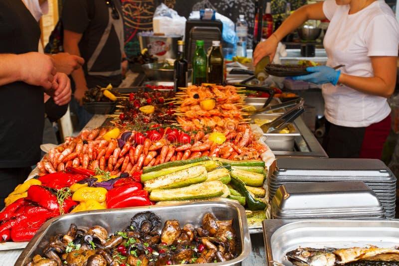 Kaufende Nahrungsmittel der Leute am Lebensmittelstall auf internationalem Festivalereignis der offenen Küche des Straßenlebensmi stockfotos