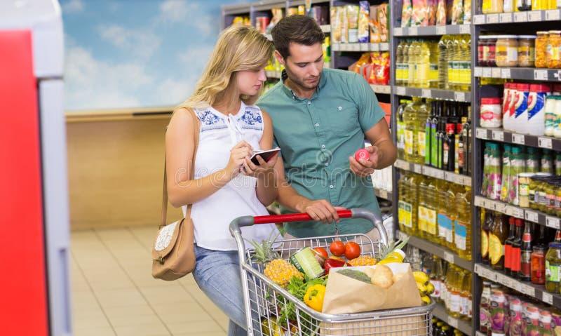 Kaufende porducts Lebensmittel der hellen Paare und mit Notizbuch stockfotos