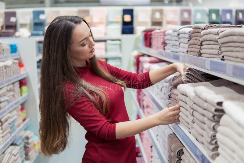 Kaufende Tücher des weiblichen intelligenten Kunden im Supermarkt stockbild