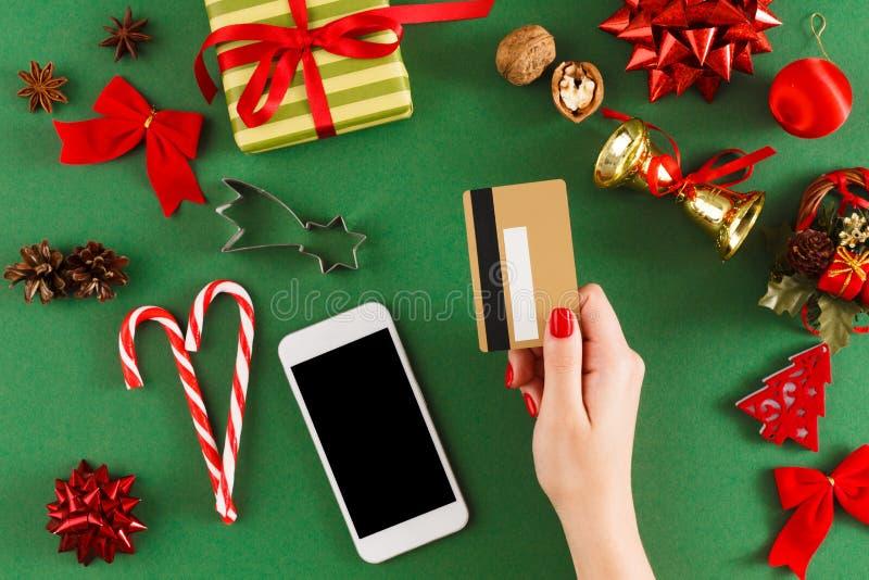 Kaufende Weihnachtsgeschenke des Mädchens online auf Smartphone mit Kreditkarte stockfoto