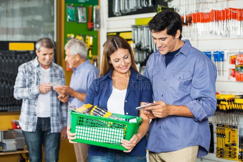 Kaufende Werkzeuge des glücklichen Paars am Baumarkt lizenzfreies stockfoto