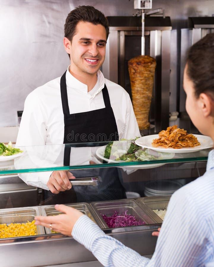Kaufender Kebab und Salat des Mädchens lizenzfreie stockfotos