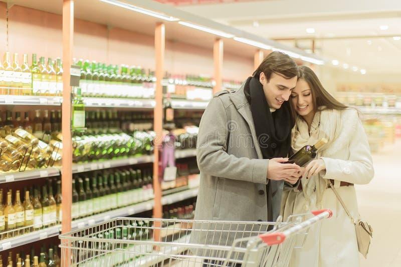 Kaufender Wein der jungen Paare stockfotografie