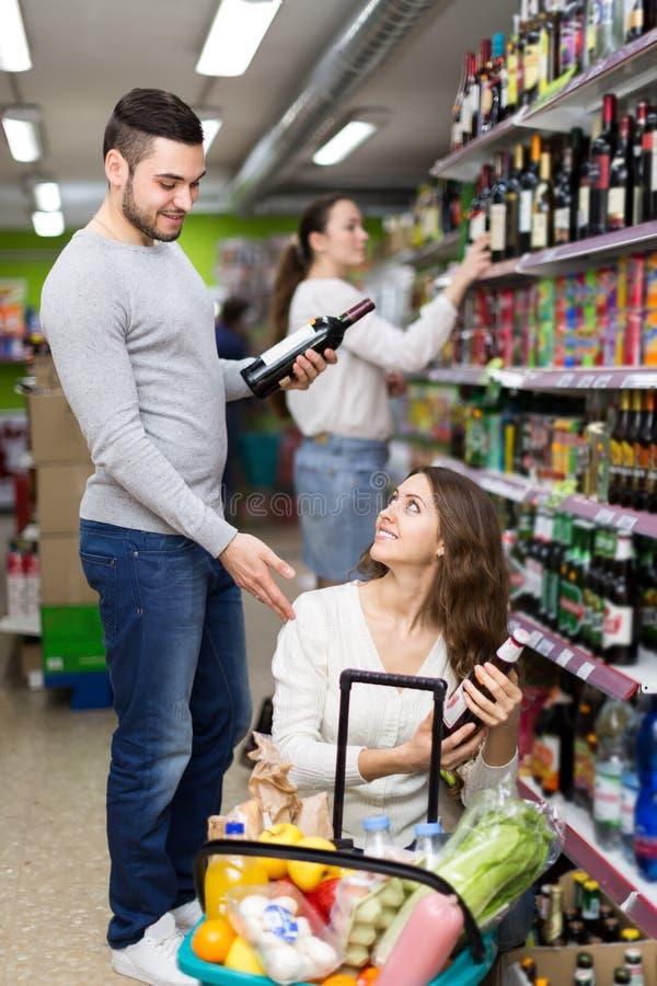 Kaufender Wein und Bier der Paare lizenzfreies stockfoto