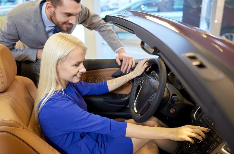 Kaufendes Auto des glücklichen Paars in der Automobilausstellung oder im Salon lizenzfreie stockbilder