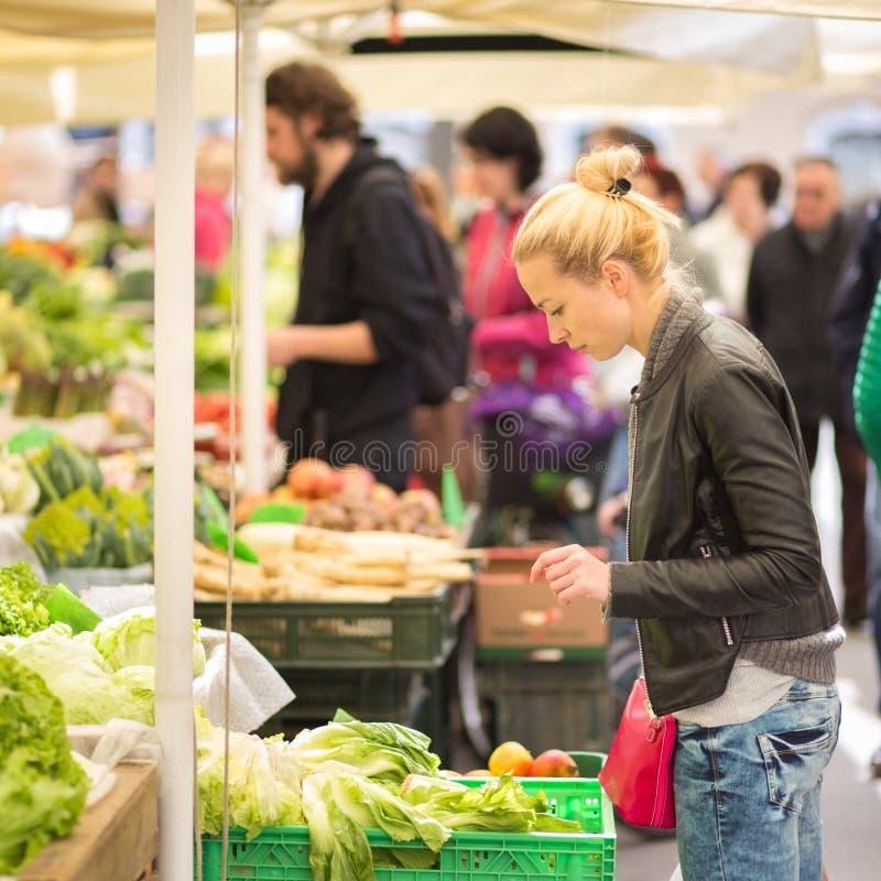 Kaufendes Gemüse der Frau am lokalen Lebensmittelmarkt lizenzfreie stockbilder