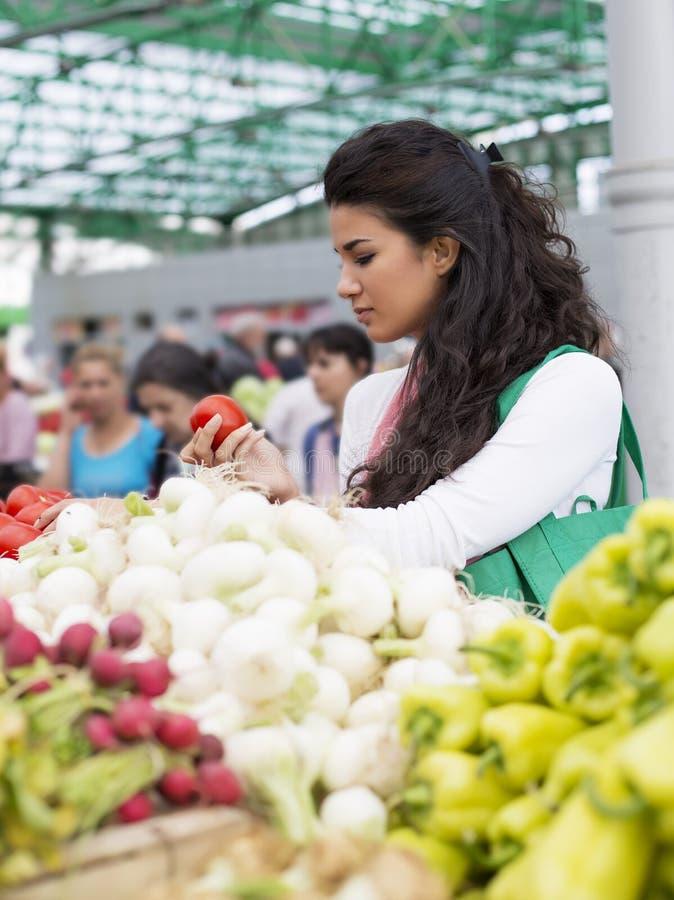 Kaufendes Gemüse der recht jungen Frau auf Markt stockfotos