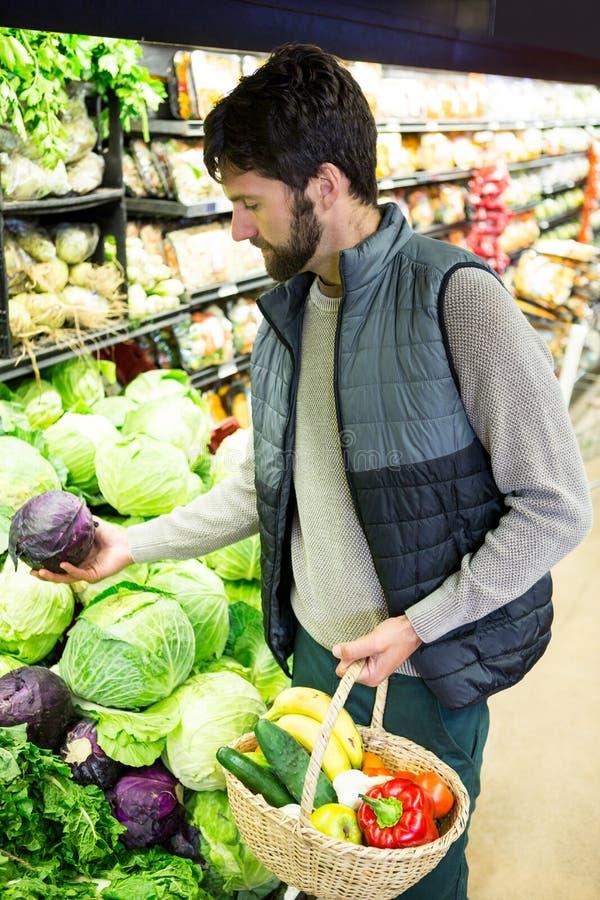 Kaufendes Gemüse des Mannes im organischen Shop stockbilder
