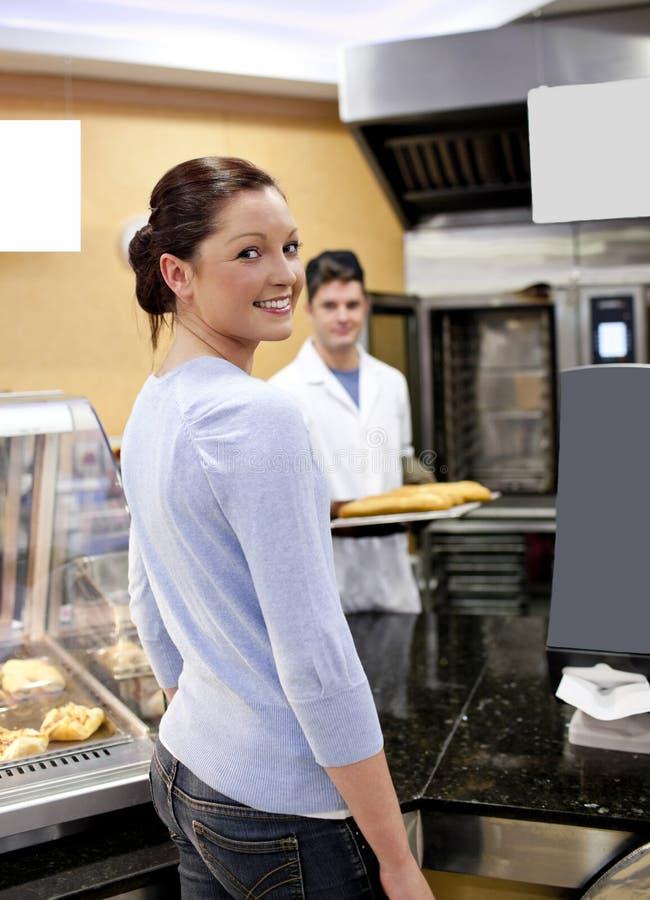 Kaufendes Stangenbrot der attraktiven Frau zu einem Bäcker lizenzfreies stockbild