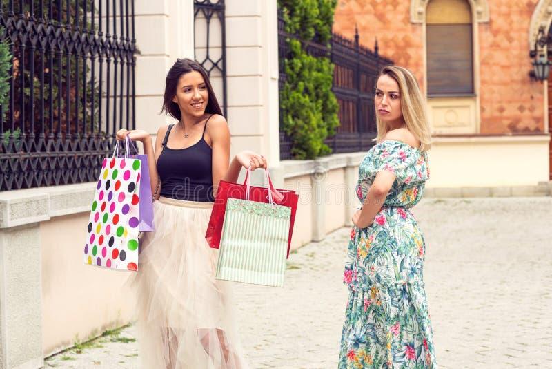 Kaufendes zeit- eifersüchtiges Fraueneinkaufen und -argumentierung lizenzfreies stockbild