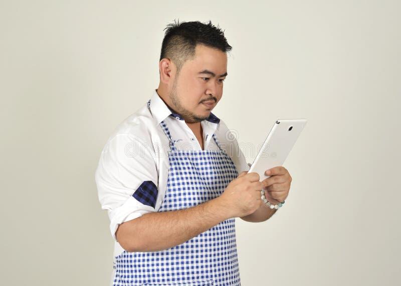 Kaufmanns-Asian-dicker Mann im weißen und blauen Schutzblech ist gelesene Datennachrichten des Gebrauches Technologie vom Verbind lizenzfreies stockbild