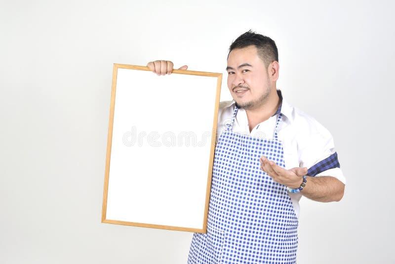Kaufmanns-Asian-Mann im weißen und blauen Schutzblech zum Halten leeres weißes breites für setzte etwas Text oder die Benennung f lizenzfreies stockbild