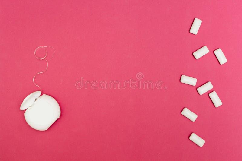Kaugummi und Zahnseide auf einem rosa Hintergrund Raum für Text stockbild