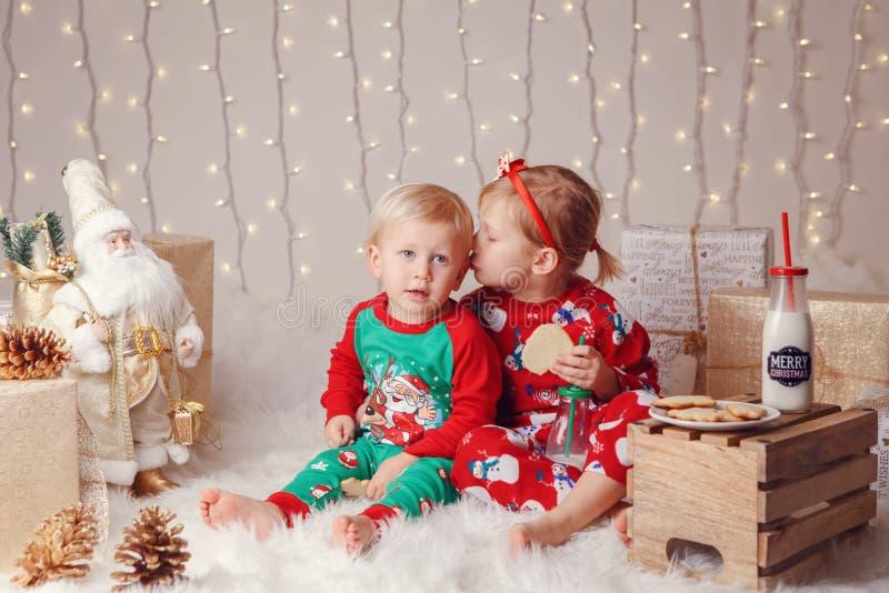 Kaukascy dzieci brat i siostra siedzi w pulowerach wpólnie ściskający odświętność nowego roku lub boże narodzenia zdjęcie royalty free