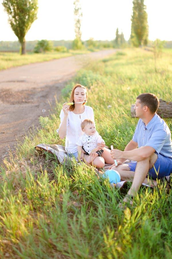 Kaukascy rodzice siedzi na trawie z małego dziecka i dmuchania bąblami obrazy royalty free