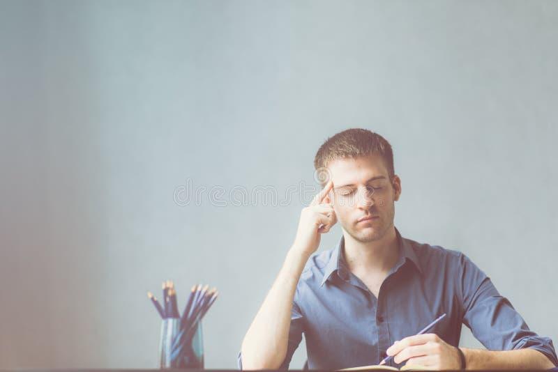 Kaukasiergeschäftsmann, der ein blaues Hemd heraus betont im Arbeitsbüro trägt Kopfschmerzen in der Planung zum erfolgreichem und stockfoto