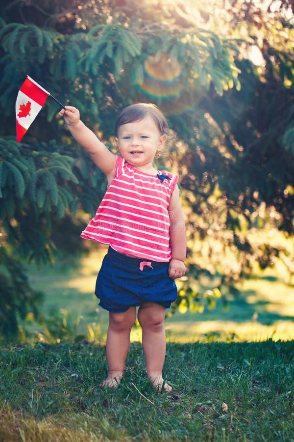 Kaukasisch babymeisje die Canadese vlag met rood esdoornblad houden royalty-vrije stock afbeeldingen