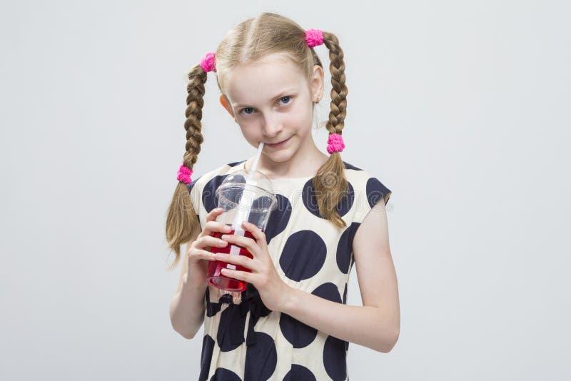 Kaukasisch Blond Meisje met Vlechten die in Polka Dot Dress Against White stellen stock afbeelding